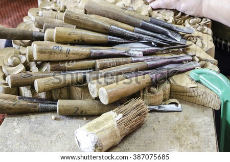 Old used wood lathe chisels selection on the dark wooden table, selective focus - stock photo