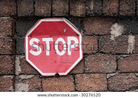 """Old useless traffic sign """"STOP"""" on a red wall from large-size blocks - stock photo"""
