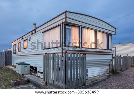 Old vacation home trailer illuminated at dusk. Trailer park in Holland, Netherlands