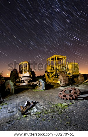 old veichle in an abandoned scrap yard at night with star trails