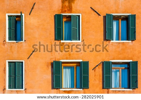 Old venetian building colorful orange painted facade with white framed facet windows - stock photo