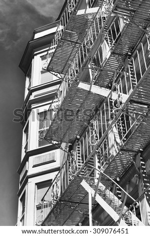 Old Victorian apartment building with fire escape in black and white - stock photo
