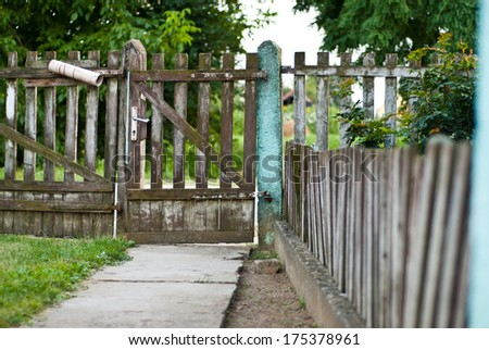 Old village wooden fence and door at the end of the yard