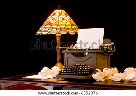 Old, vintage, antique, typewriter in writer's or author's work space with desk lamp, illustration of writer's block - stock photo