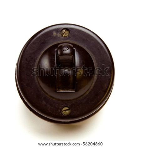 Old Vintage bakelite light switch isolated against white background from low perspective. - stock photo