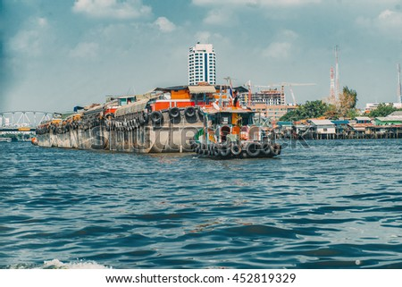 Old vintage barge carrying delivering cargo across the river. Vivid industrial background. Chao Phraya river. Bangkok, Thailand. Vintage effect. - stock photo