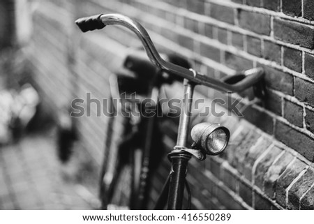 Old vintage bicycle front light detail near modern building. Shallow focus.