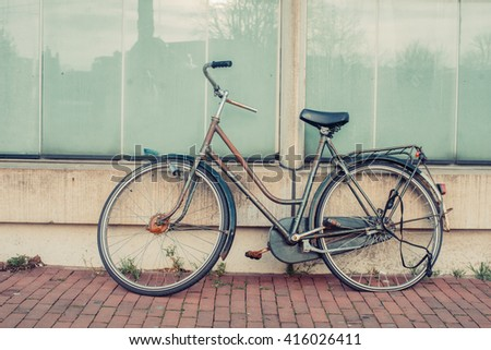 Old vintage bicycle on modern futuristic building background. Vintage effect. Sunset.