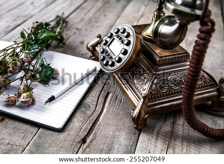 Old vintage black rotary phone and a bouquet of roses on wooden background - stock photo