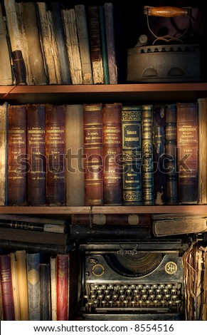 Old vintage books and typewriter in a row - stock photo