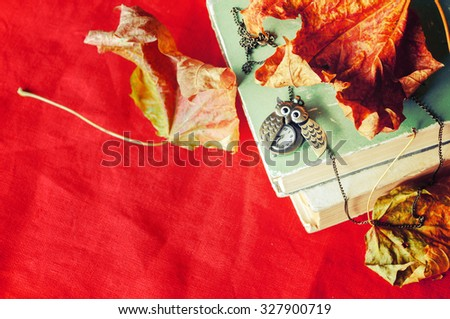 Old vintage  books with bronze clock in form of owl between pages on the red linen tablecloth with dry yellow maple leaves.  Selective focus at the clock - shallow depth of field - stock photo