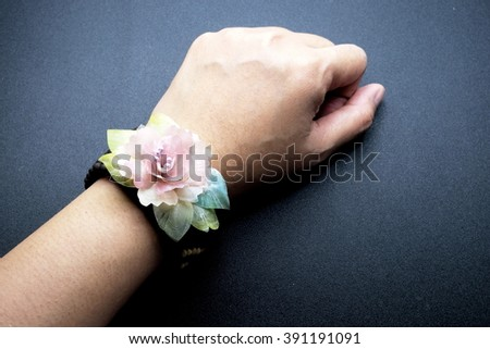 Old vintage bracelet with sweet color flower from fish scale on wrist female on black background. Dark tone.
