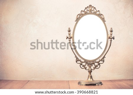 Old vintage bronze makeup mirror frame on table. Retro style filtered photo - stock photo