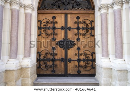 Old vintage building entrance door made of wood with metal enhancements. - stock photo