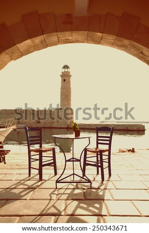 Old vintage cafe and lighthouse on the sea  Rethymnon Crete, impressions of Greece - stock photo