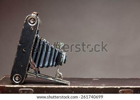 Old vintage camera lying on suitcase on gray background - stock photo