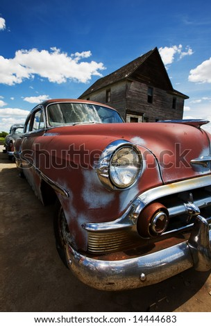 Old vintage cars left to rust in a ghost town - stock photo
