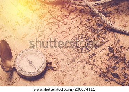 Old vintage compass on vintage map and rope. Vintage filter. - stock photo