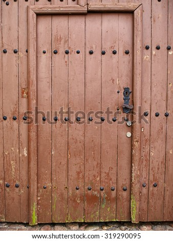 Old vintage decorated wooden brown door as an entry to a city house - stock photo