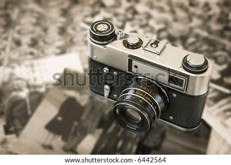 Old vintage film camera sitting on top of old black and white photos - stock photo