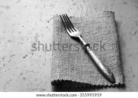 Old vintage fork on a linen napkin on a grey background. Top view. Black and white photo. Free space for text. Copy space