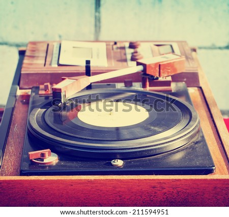Old vintage good looking turntable playing a track with vinyl. - stock photo