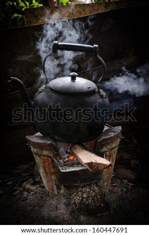 Old vintage Kettle put on a fireplace - stock photo