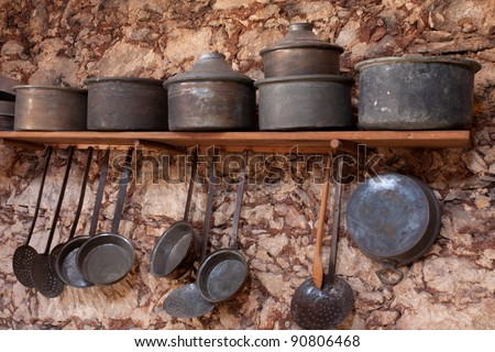 Old, vintage kitchenware against a stone wall - stock photo