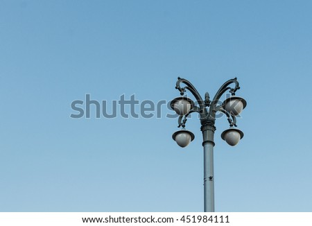 Old vintage lamp post on blue sky background - stock photo