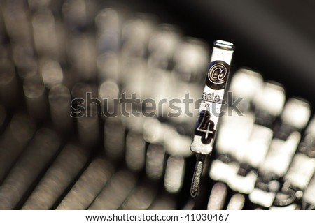 Old vintage manual typewriter hammers with focus on the at symbol - stock photo