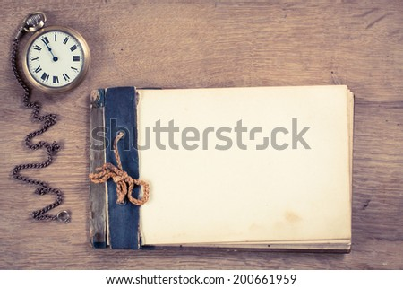 Old vintage notebook blank, bronze pocket watches on wooden table - stock photo