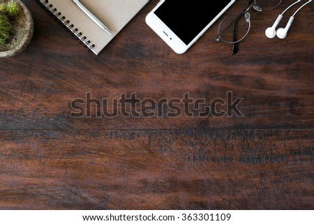 Old vintage office desk table with notebooks, pen, smartphone with earphone and eye glasses. Top view with copy space. - stock photo