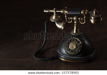 Old vintage or antique rotary phone with a handset and cradle on a dark shadowed background with copyspace