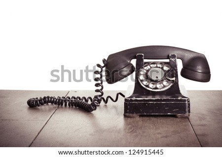 Old vintage phone with rotary disc on wooden table grunge background