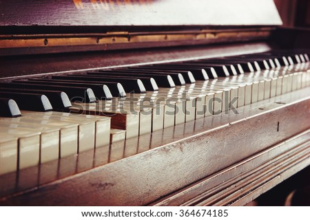 old vintage piano keyboard, one key is pressed, music concept in warm color toned retro style, selected focus and shallow depth of field - stock photo