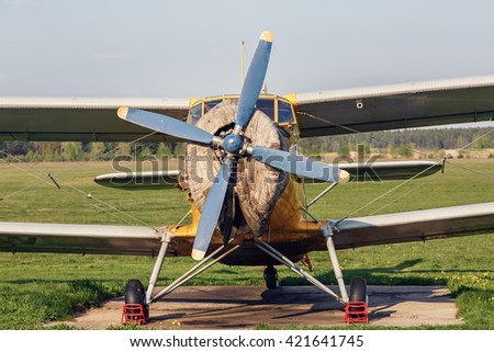 Old vintage plane. Retro airplane. Vintage single-engine plane with a propeller. Old biplane. Front view, with the side of the fuselage. - stock photo