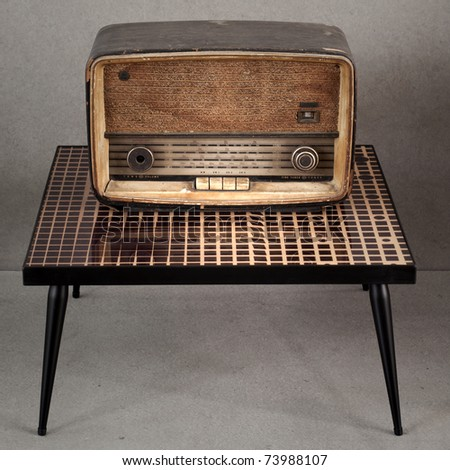 Old vintage radio on old table - stock photo