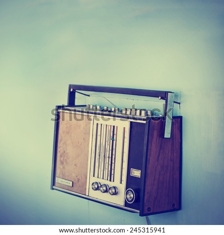 Old vintage radio over wall/old dirty tuner in vintage color,selective focus - stock photo