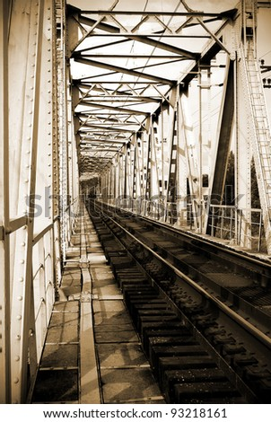 Old vintage railway bridge over river. Sepia - stock photo