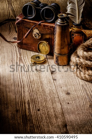 Old vintage retro compass, binoculars and spyglass on wooden table. Vintage still life. Travel geography navigation concept background.