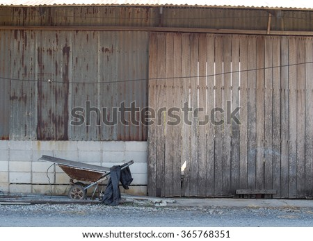 old vintage retro easy constructed country agricultural farm house wall side elevation view with large wooden slide door, brick wall galvanized metal sheet and a rustic iron push cart  - stock photo