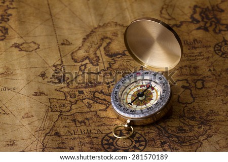Old vintage retro golden compass on ancient map. - stock photo