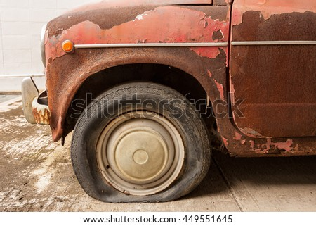 Old vintage rusty car showing detail from the front. - stock photo