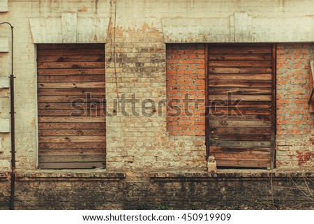 Old vintage sealed windows on the worn peeled yellow brick wall. Abandoned factory warehouse. Industrial texture background. Soviet architecture.