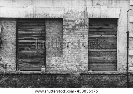 Old vintage sealed windows on the worn peeled yellow brick wall. Abandoned factory warehouse. Industrial texture background. Soviet architecture.  - stock photo