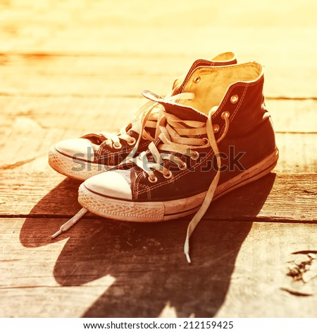 Old vintage sneakers closeup on a sunny day - stock photo