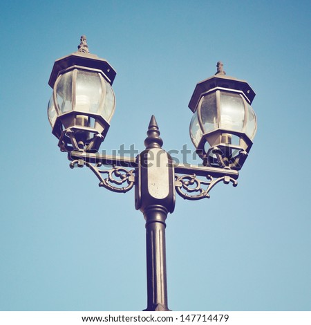 Old vintage street light against blue sky with retro filter effect - stock photo