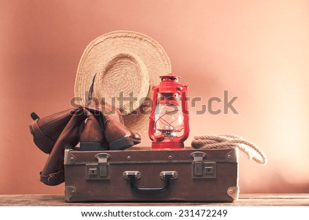 Old vintage suitcase and leather footwear with stetson and kerosene lamp - stock photo