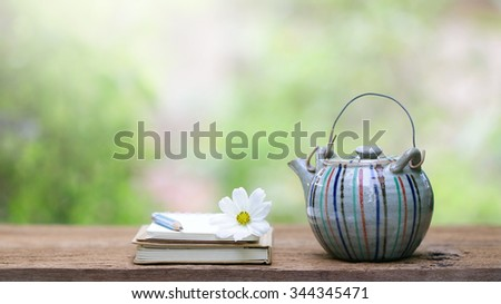 Old vintage teapot and notebooks at outdoor - stock photo