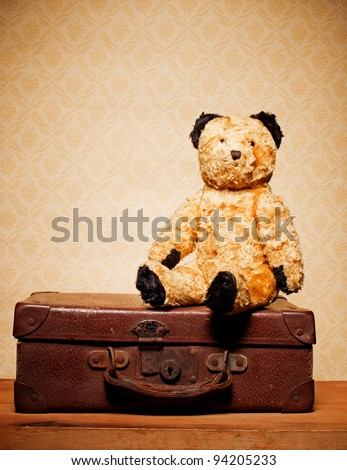 Old vintage teddy bear and old leather suitcase, bygones and memorabilia. - stock photo